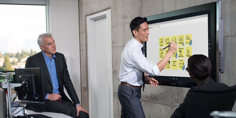 Business man using touch screen pen to present to coworkers
