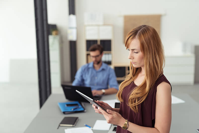 Businesswoman using cloud technology on tablet in open office