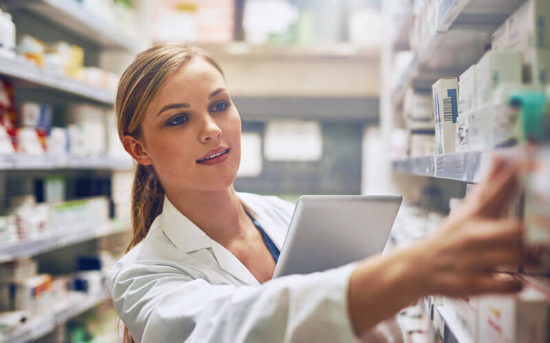 Woman pharmacist in Pharmacy with tablet device