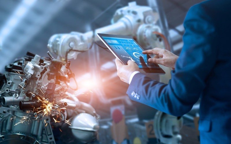 Business professional using tablet to monitor manufacturing